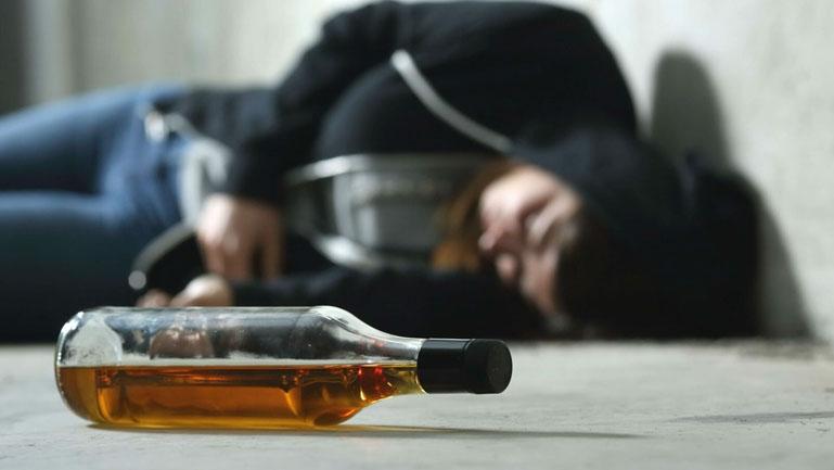 Jovem caído no chão ao lado de uma garrafa de bebida representando uma pessoa embriagada.