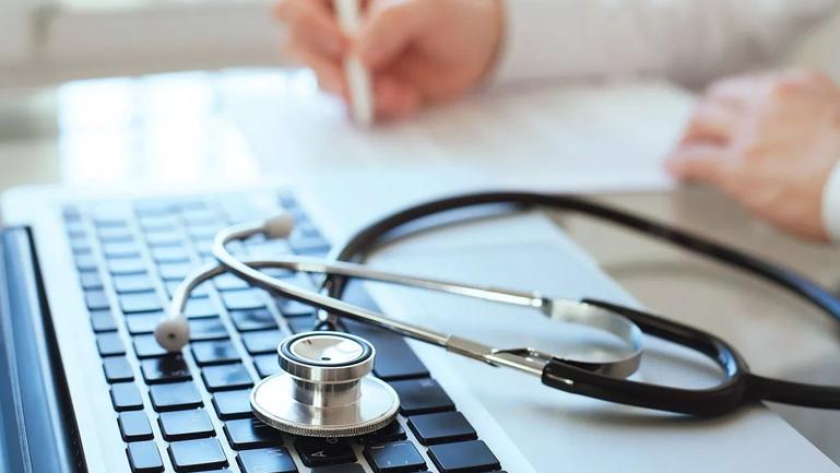 Laptop com um estetoscópio em cima para falar sobre a agenda médica.