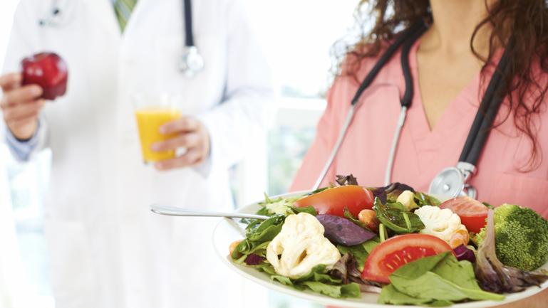 Enfermeira com um prato de comida saudável para falar sobre a boa alimentação de médicos.