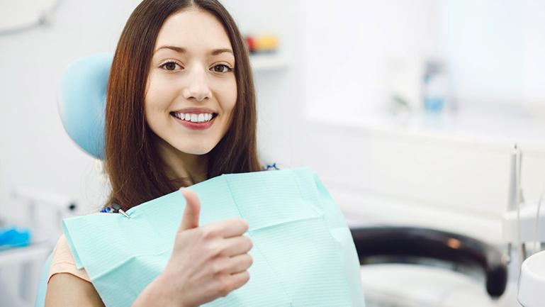 Paciente fazendo um sinal positivo em consultório dentário para representar as vantagens de um plano odontológico.
